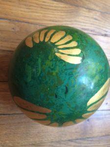 boule Printemps en laque coté grande pétale travaillée en feuilles d'or. Cette boule en bois dispose de l'autre coté via des pigments verts et des pétales en pigments rouge orangés  creation de pièce unique en laque
