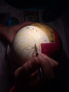 délicat travail de décor sur une boule pour rehausser la forme blanche et indiquer les plumes formant le plumet, oeuvre unique en laque avec de l'or